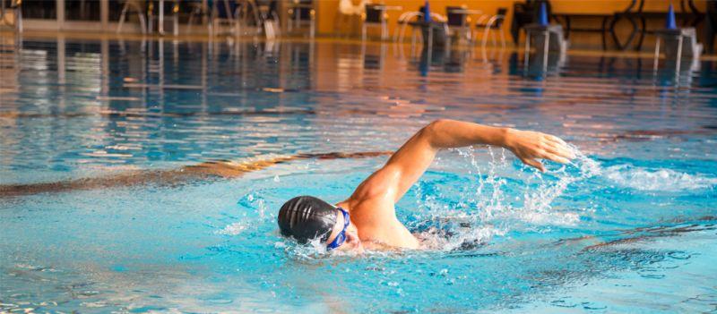 Nadador tumbado sobre el borde de una piscina estirando